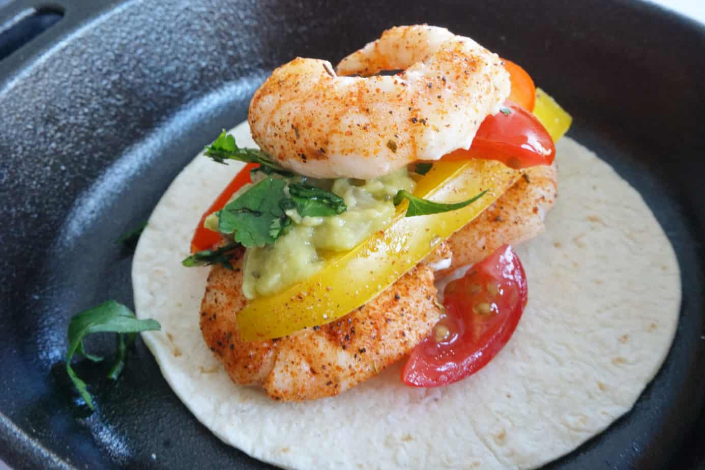 shrimp fajitas with seasoning, guacamole and cilantro on a low carb taco shell