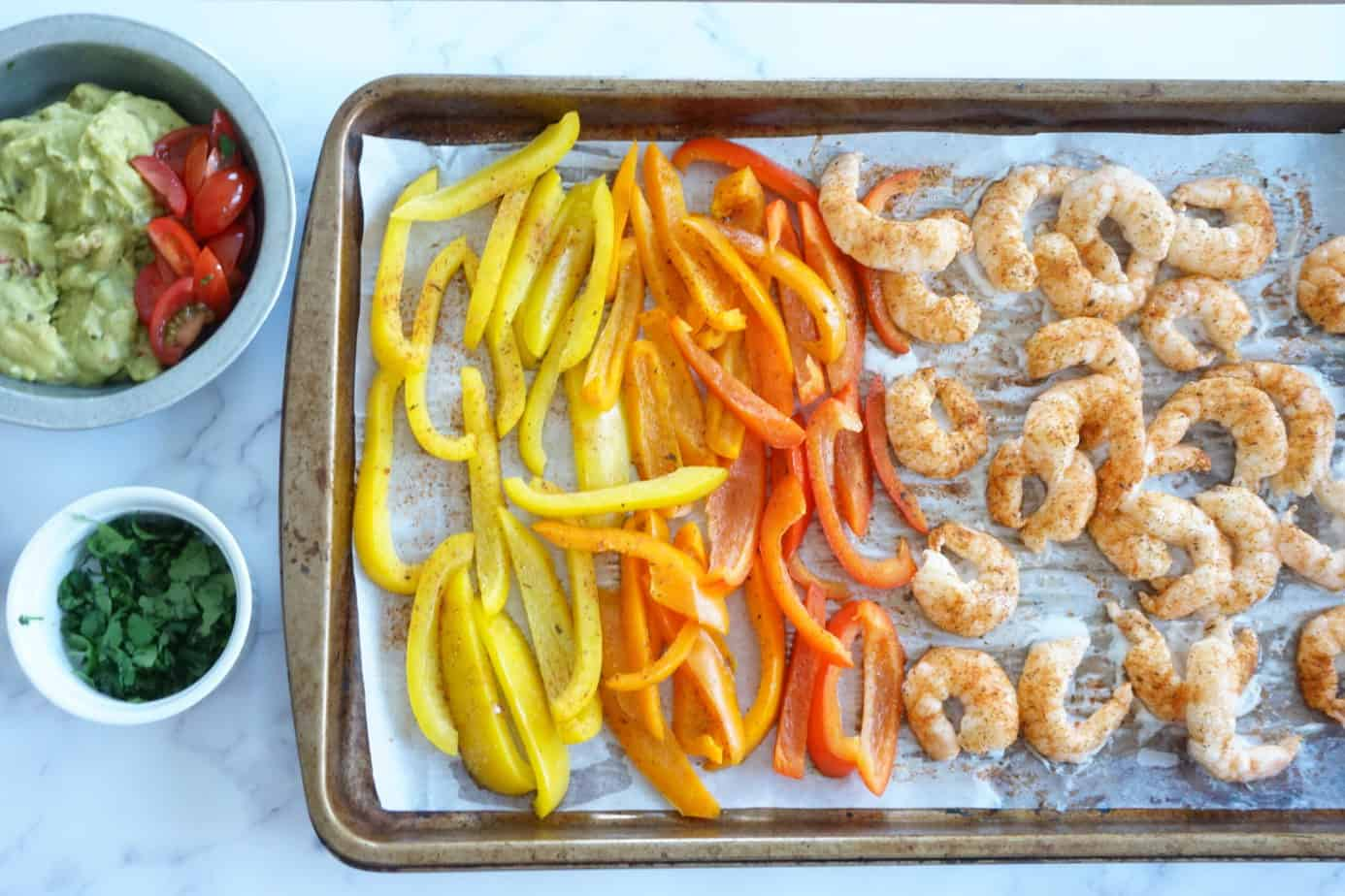 shrimp fajitas with seasoning, guacamole and cilantro