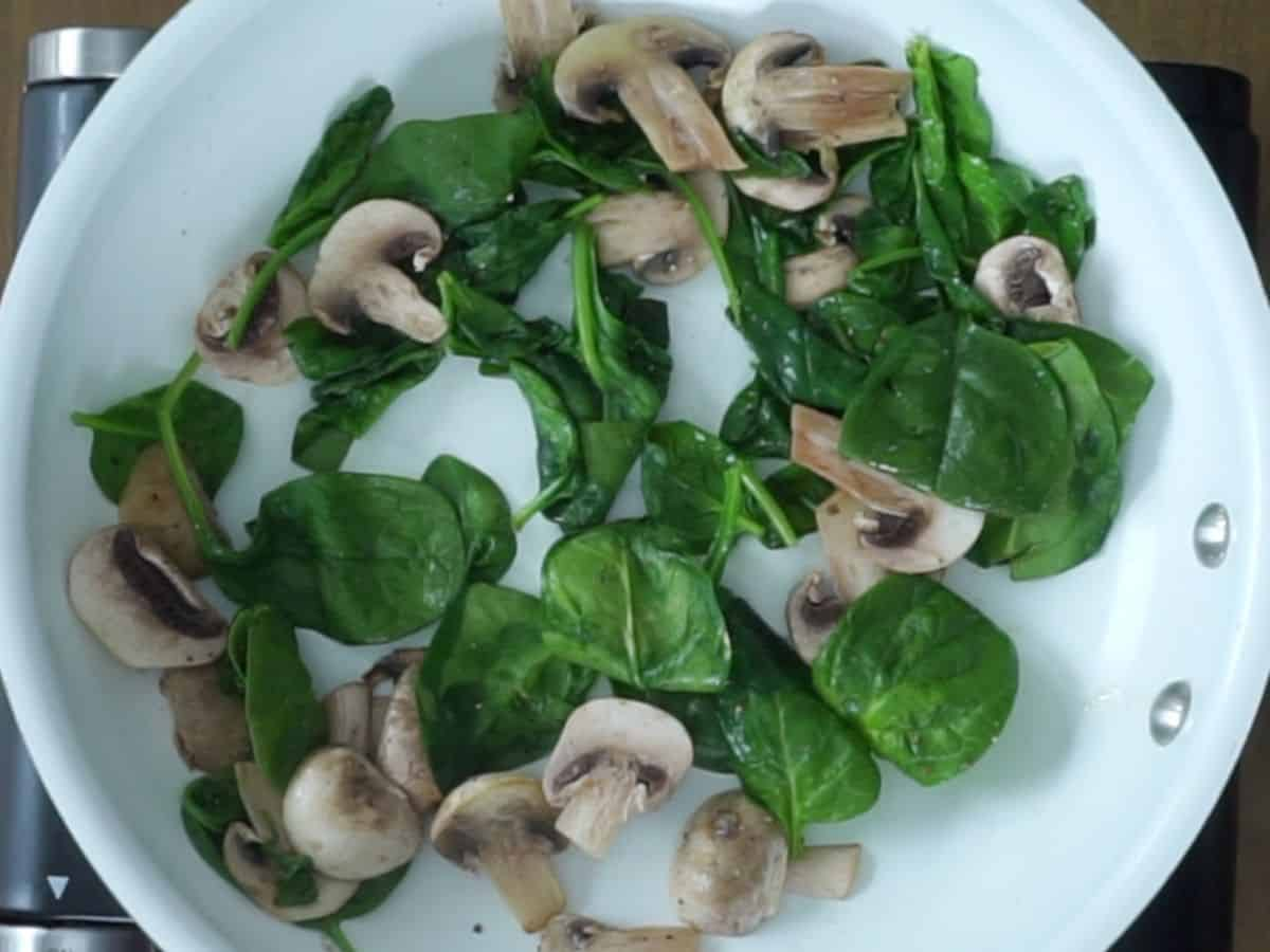 cooked spinach and mushrooms in frying pan