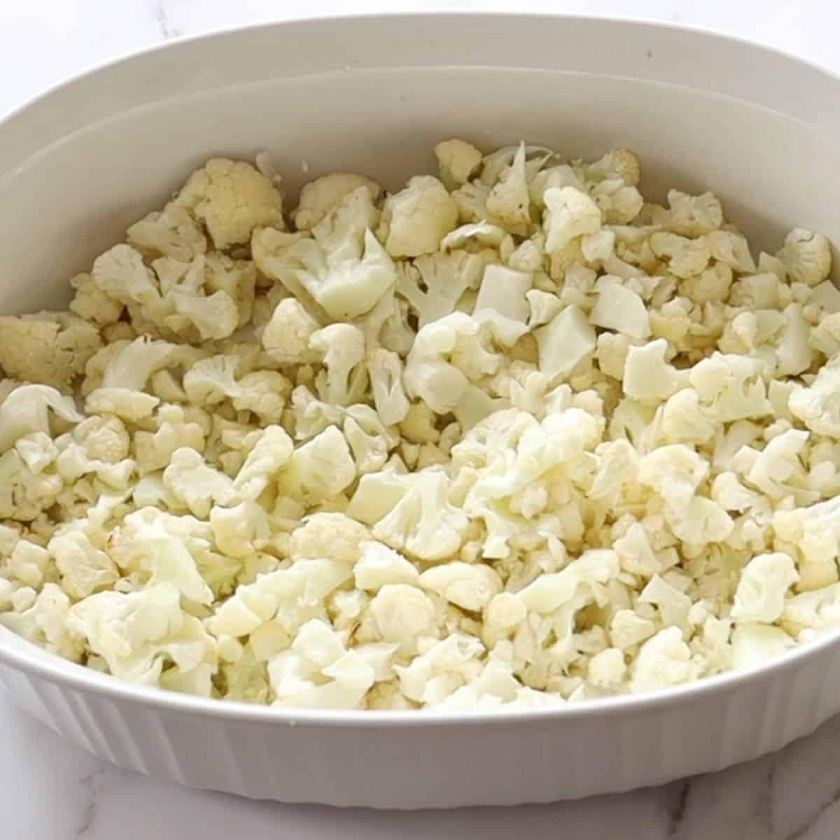 add roasted cauliflower to baking dish