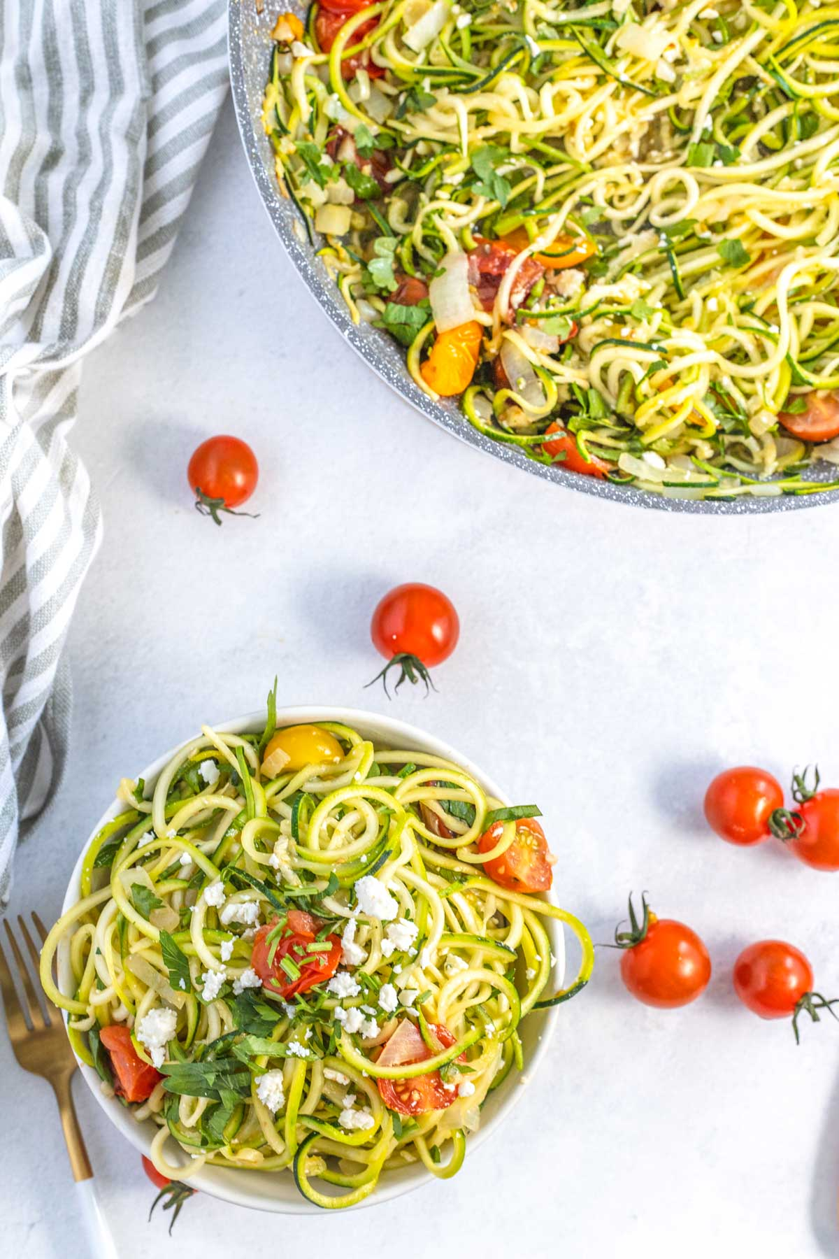 fresh parsley and feta atop zucchini pasta in a bowl