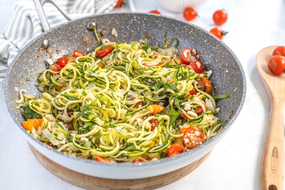 large frying pan with zucchini pasta, cherry tomatoes and parsley