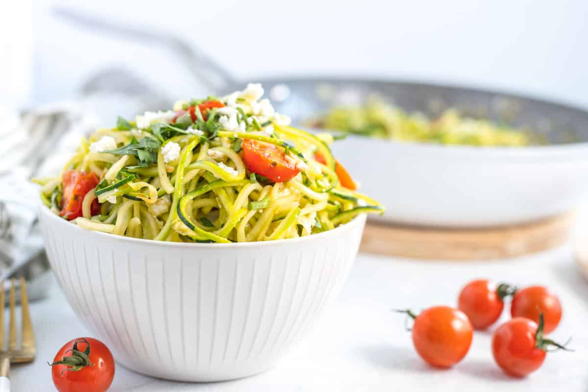 bowl of zoodle pasta with cherry tomatoes, feta cheese and fresh parsley
