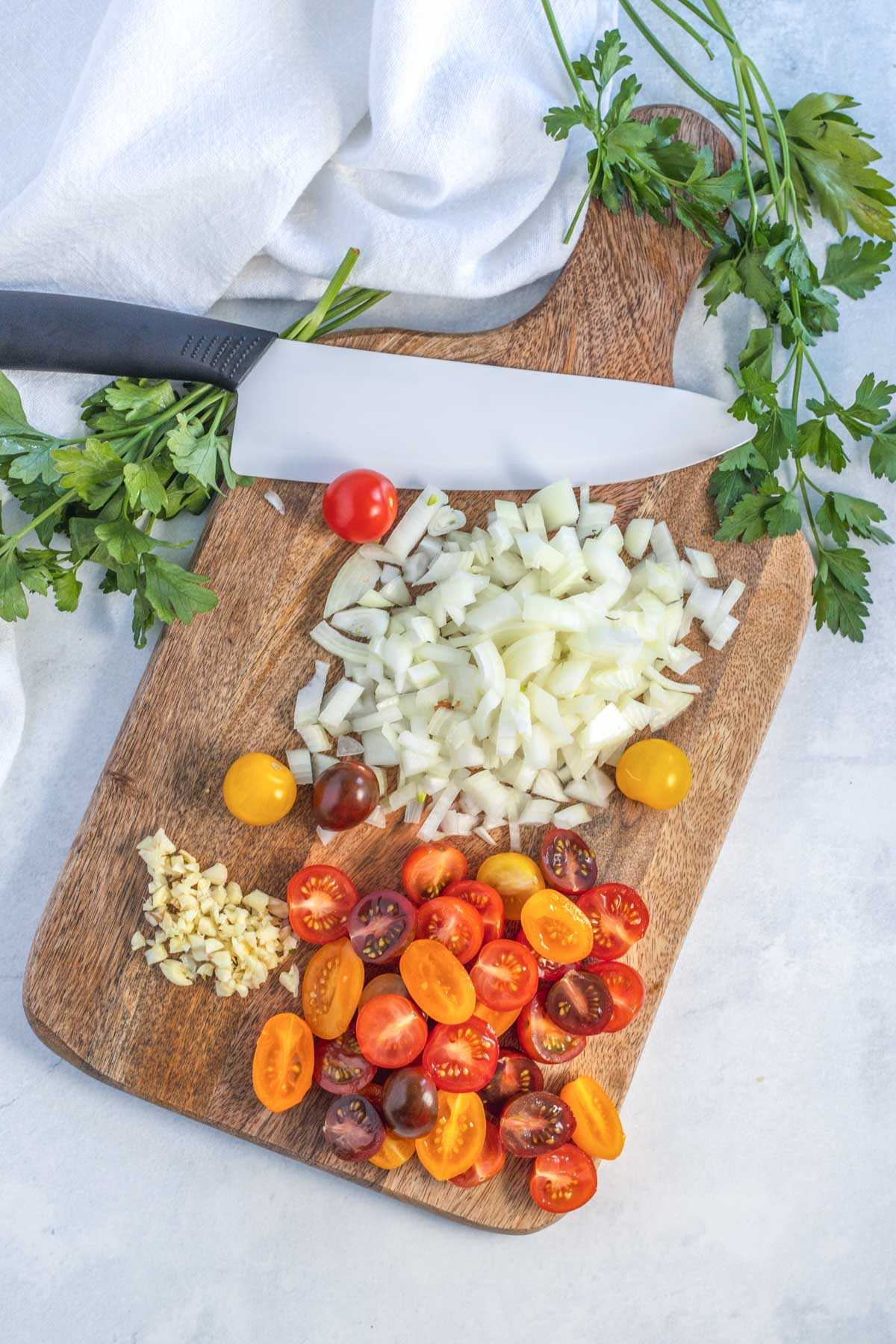 chopping garlic, tomatoes and onion on a cutting board