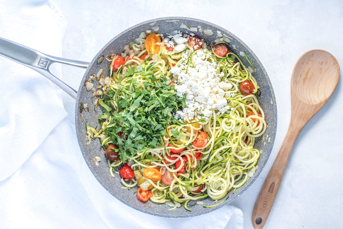 frying pan with zoodles, cherry tomatoes, feta cheese and fresh parsley