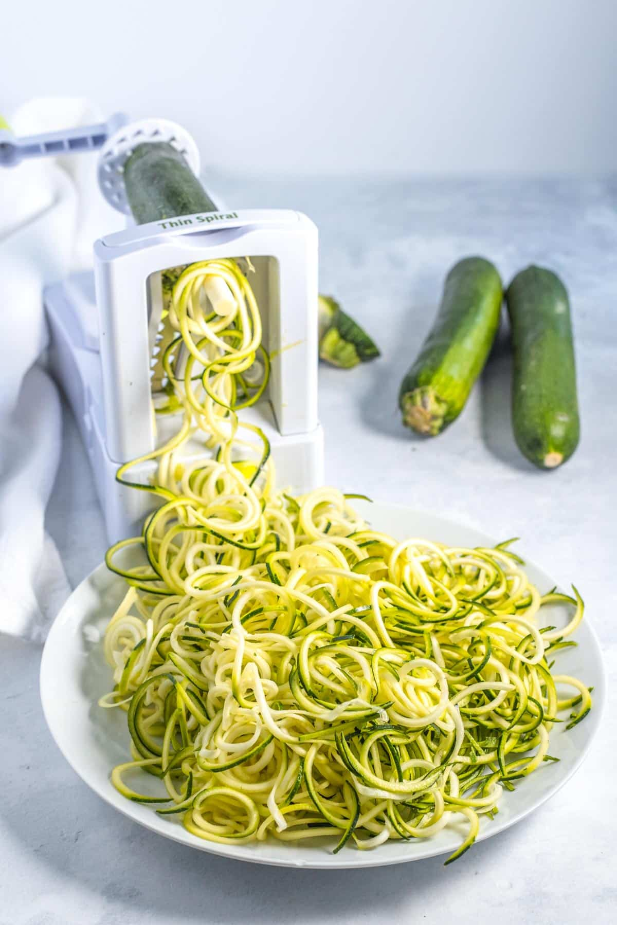 spiralizer with zucchinis making zoodles, zucchini noodle pasta