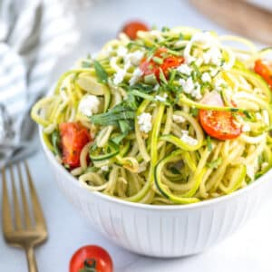 bowl of zucchini feta pasta with zoodle spirals, cherry tomatoes, and fresh parsley