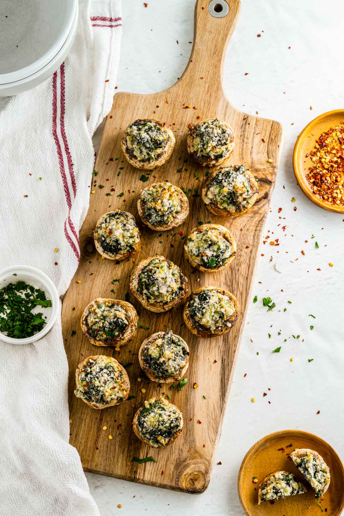 wooden tray with seasonings and a dozen stuffed mushrooms