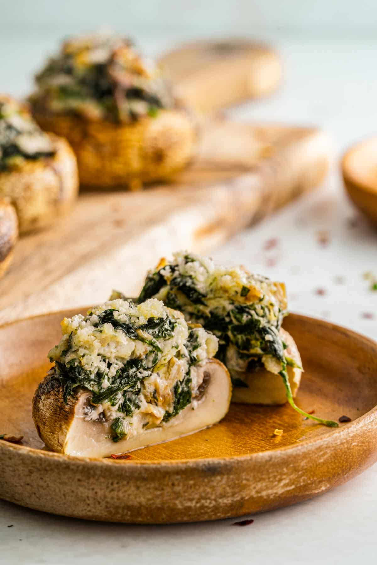 mushroom cut open revealing creamed spinach and parmesan cheese inside