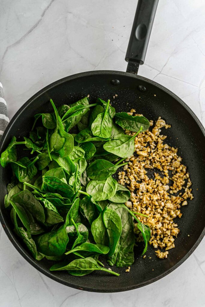sautéed spinach with chopped mushrooms in a frying pan
