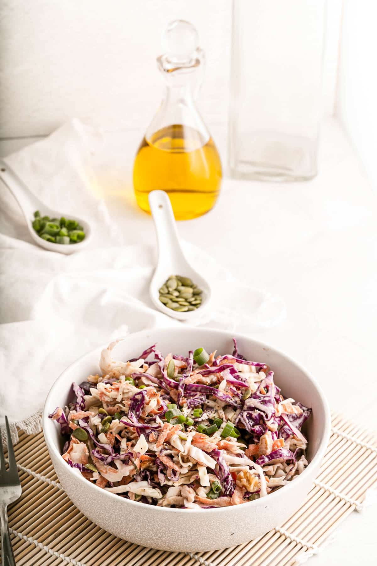 coleslaw in a bowl on a bamboo mat with seeds