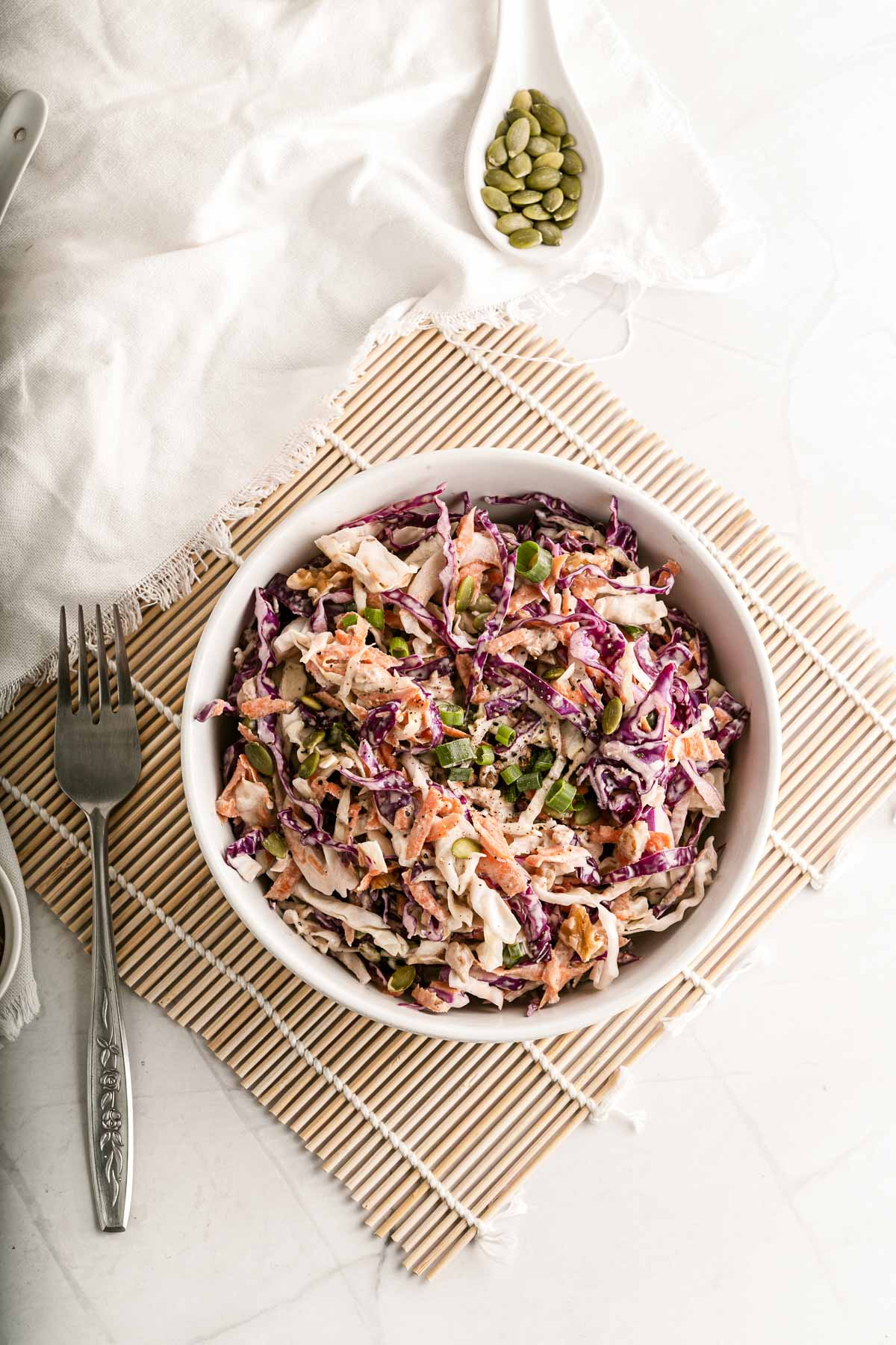 coleslaw in a bowl with a fork and pumpkin seeds