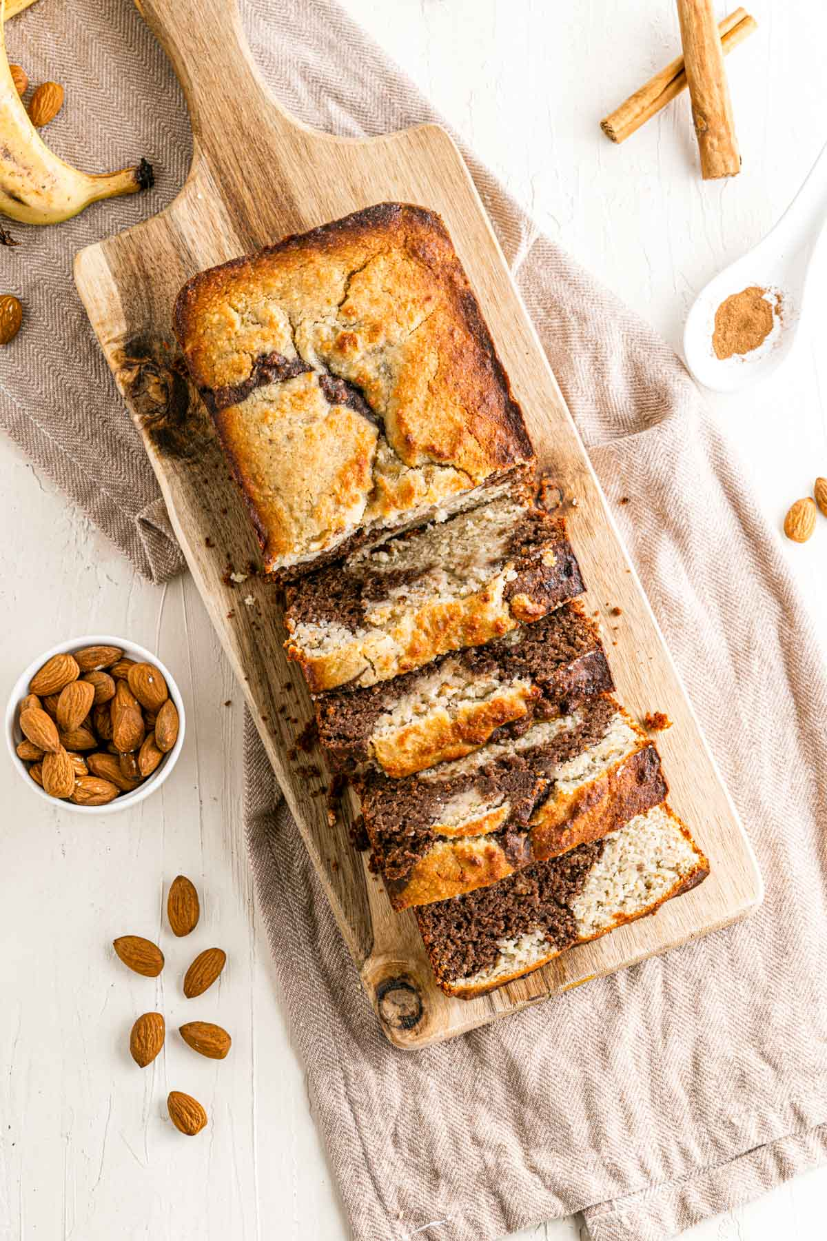 overhead view of baked banana bread with chocolate swirls and almonds