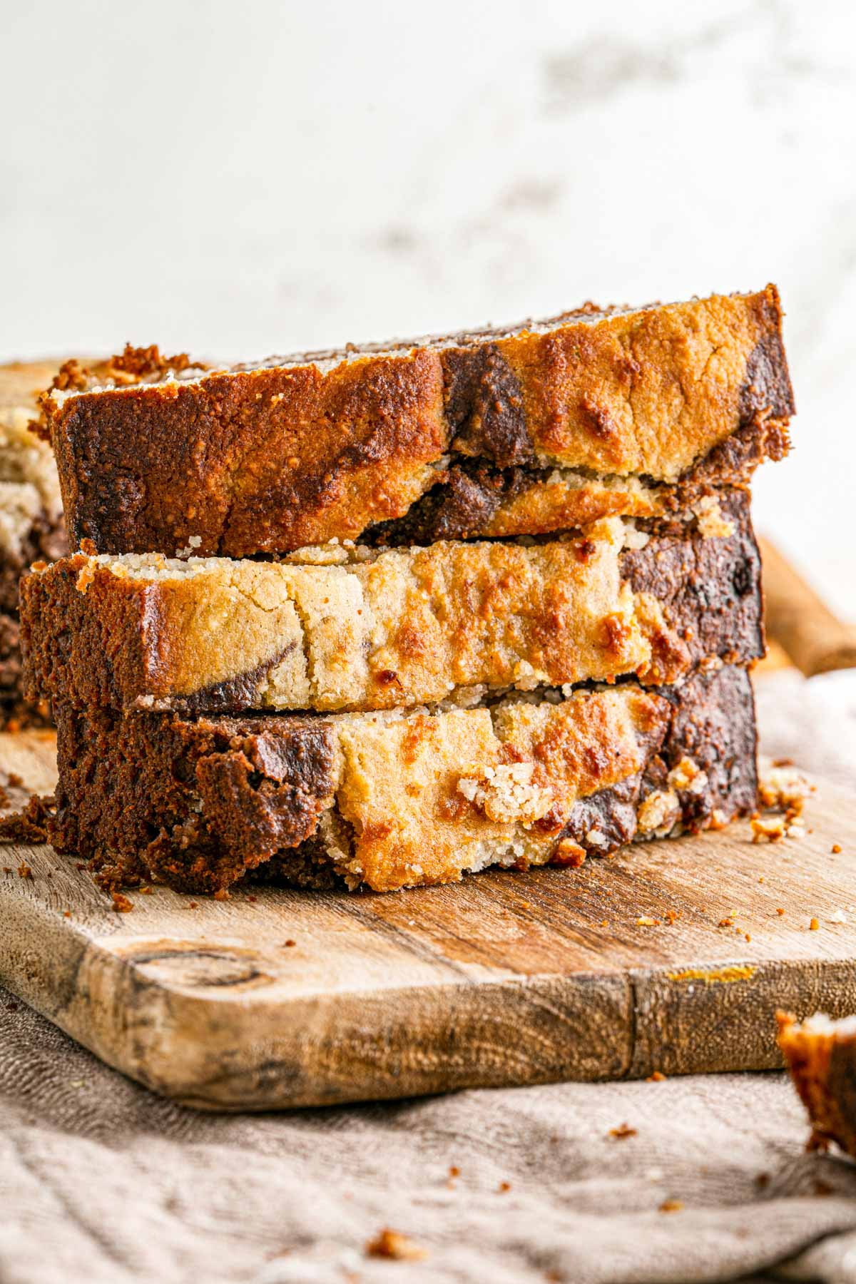 three slices of banana bread stacked in a pile on a wooden cutting board
