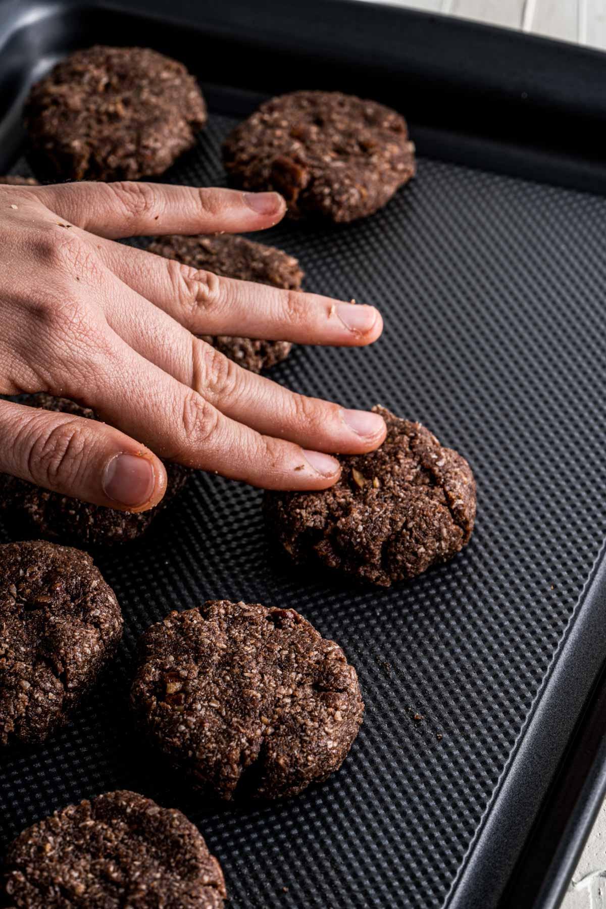 pressing cookies onto a metal pan