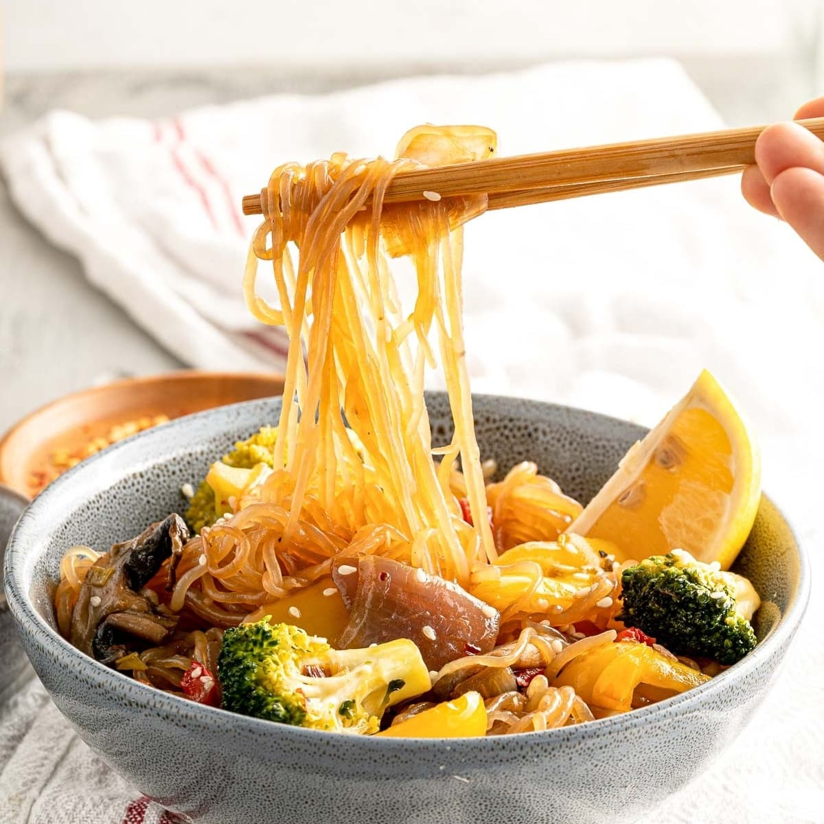 chopsticks lifting shirataki noodles covered in stir fry sauce with veggies in a bowl