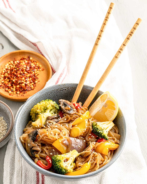 bowl of stir fry ingredients with chopsticks