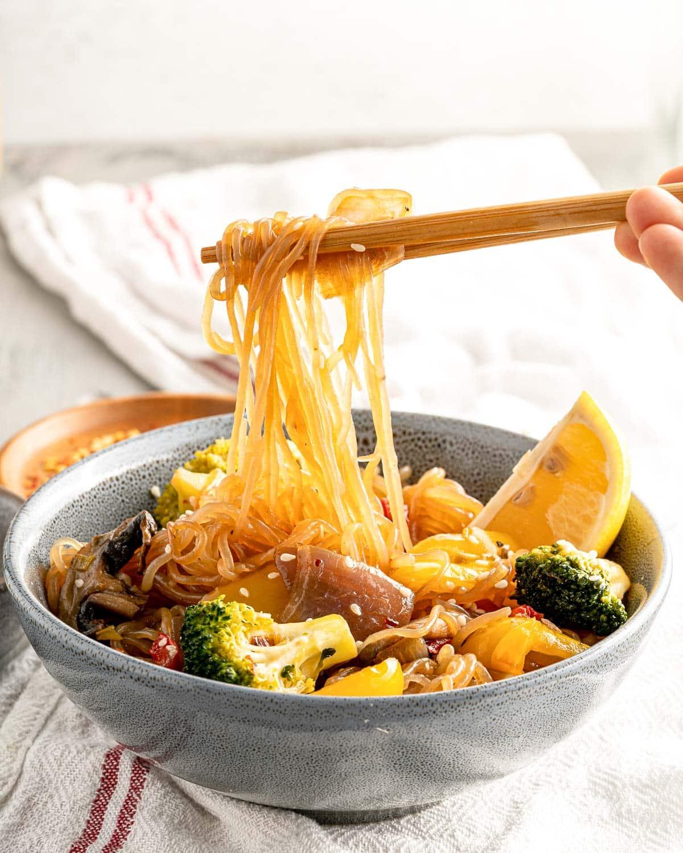 low carb shirataki noodles with chop sticks and a bowl of stir fry veggies
