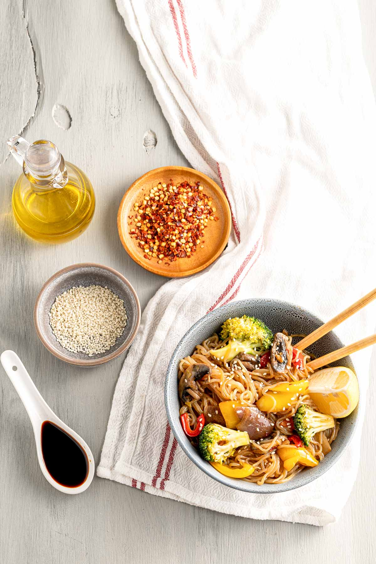 bowl of stir fry with ingredients on a table with a tablecloth, oil, noodles, and soy sauce