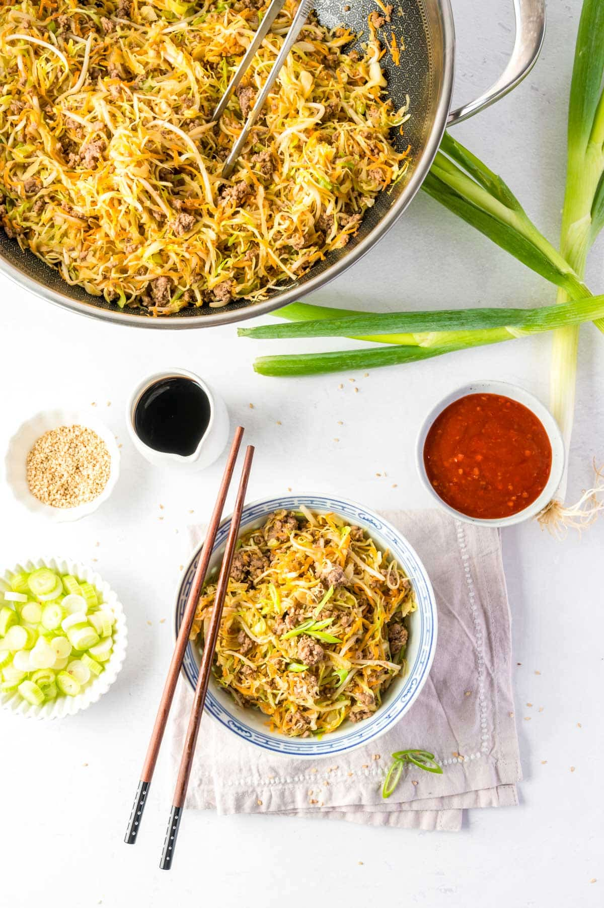 bowl with cabbage stir fry and sauce, chopsticks, wok, and green onion