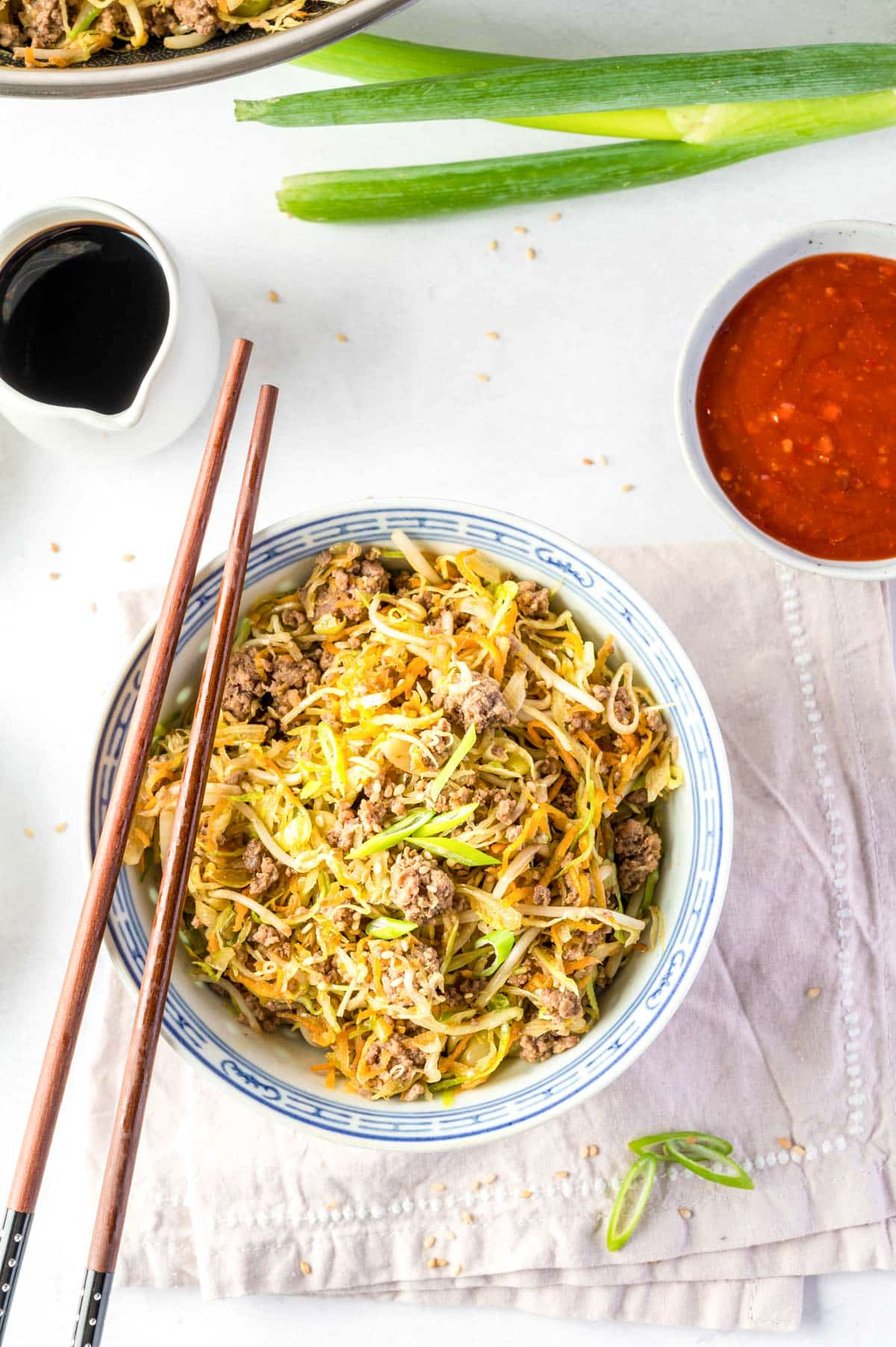 egg roll bowl with chopsticks, green onion, and sauce