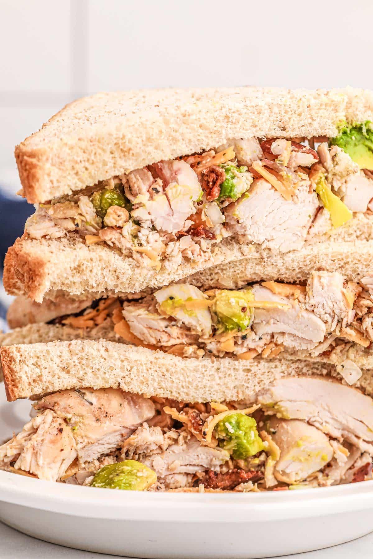 stack of chicken salad sandwiches cut open