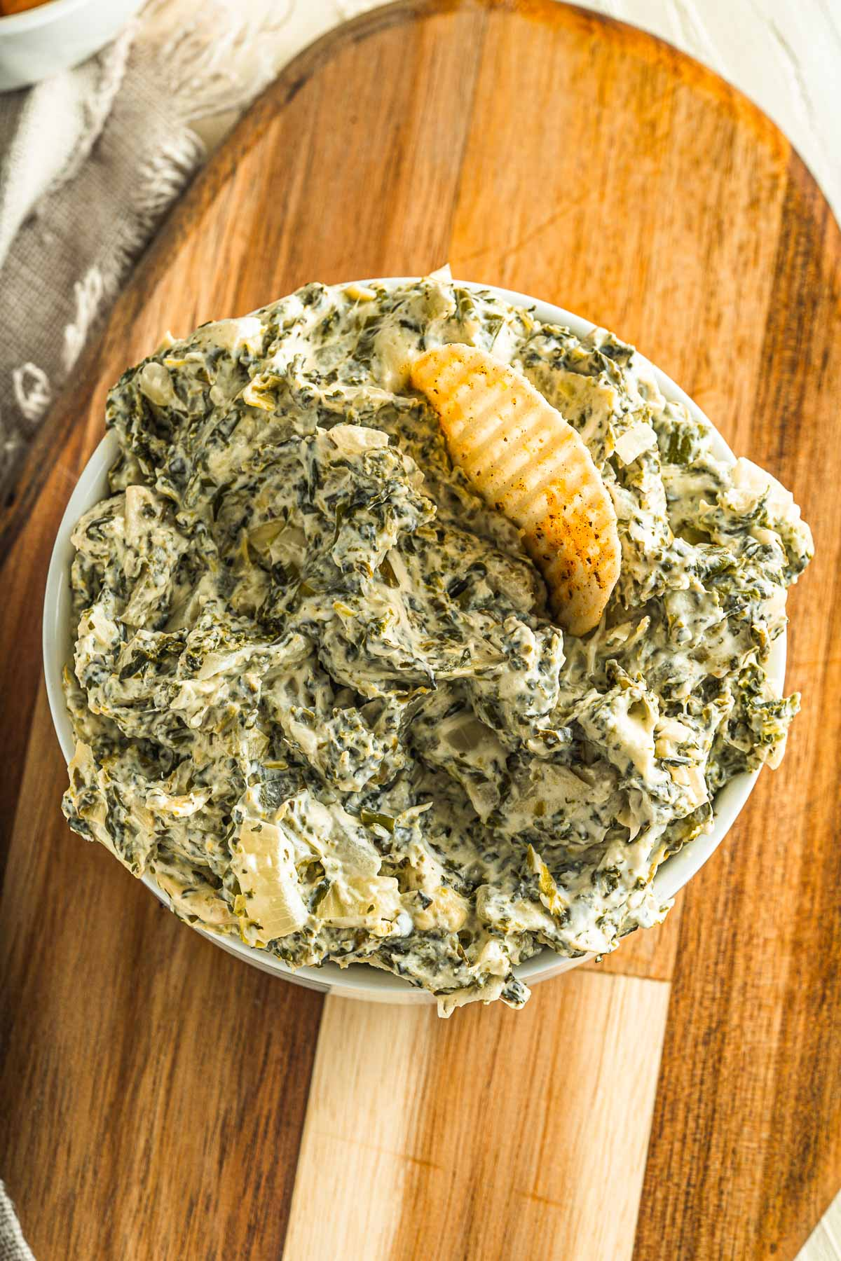 serving bowl with spinach artichoke dip and a chip