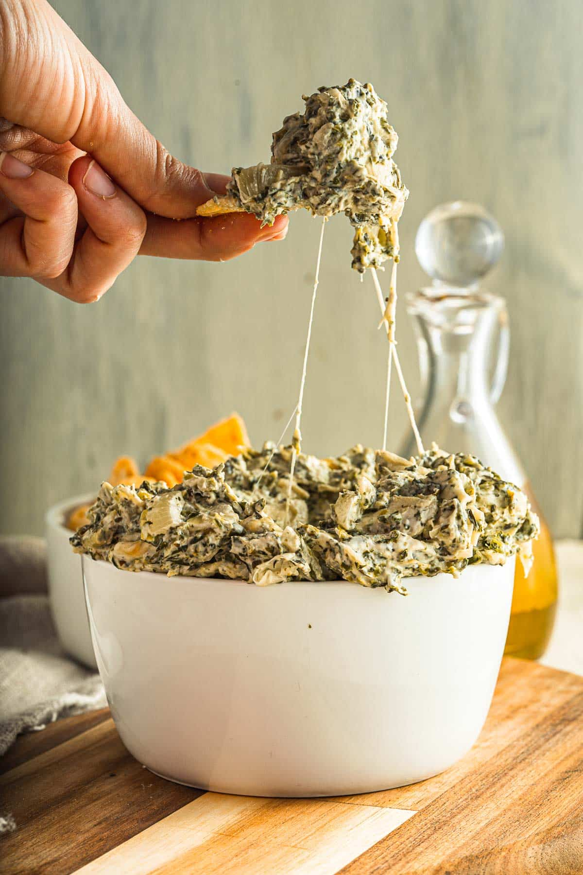 spinach artichoke dip being scooped up from a bowl with strings of cheese