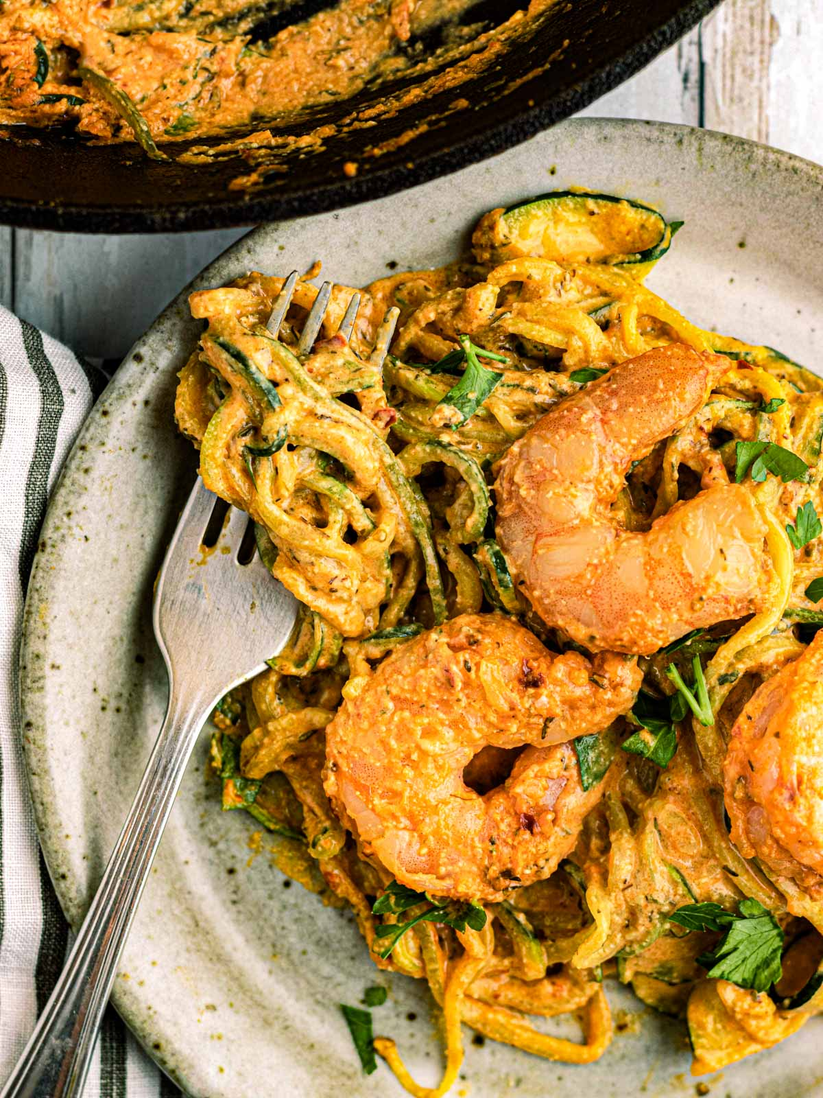 shrimp and zoodles in a dish with a fork