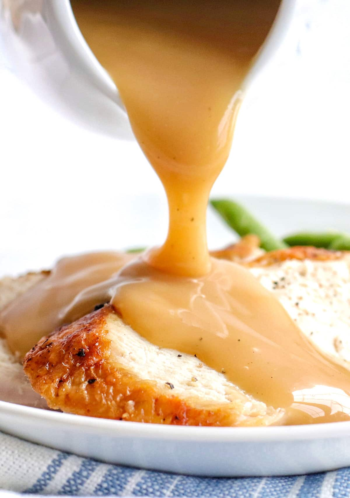 air fryer turkey breast slices with brown turkey gravy pouring over them