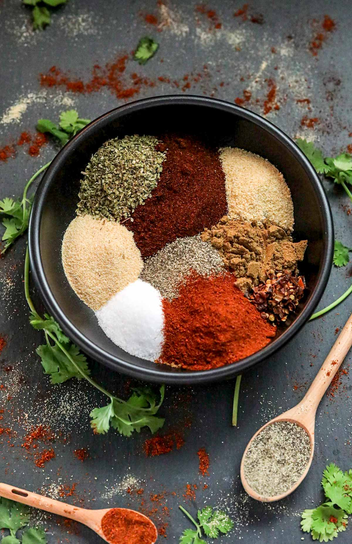 seasonings in a large bowl with spoons and Mexican spices