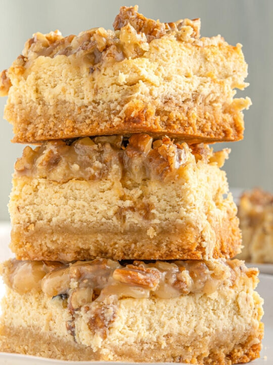 thick keto cheesecake bars stacked in a pile of three