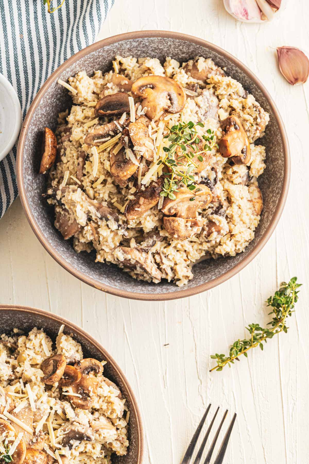 riced cauliflower with creamy sauce and mushrooms in two bowls on a white table