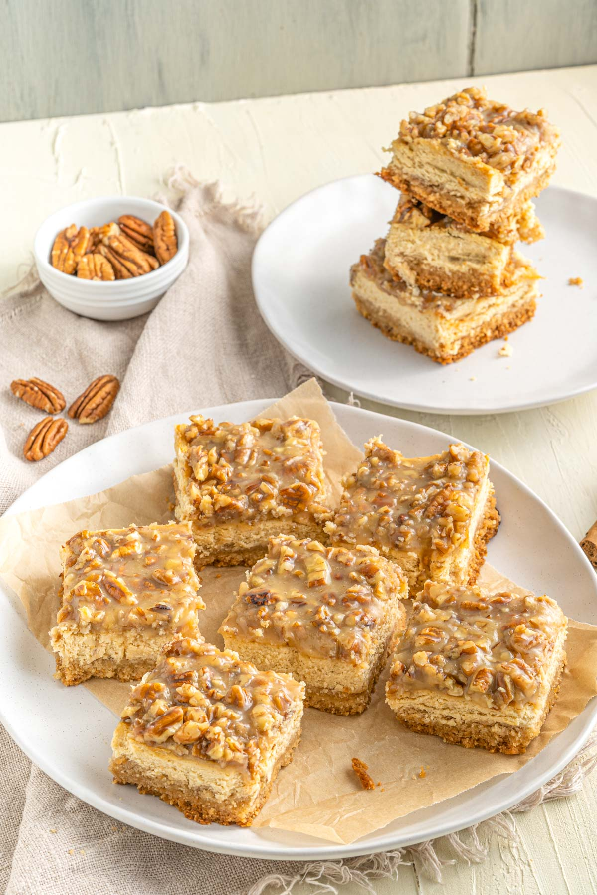 cheesecake bars spread out on a table with pecans