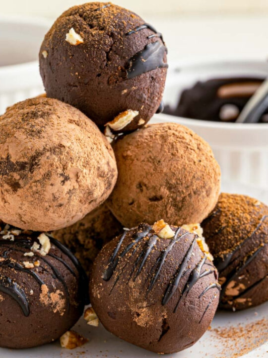 stack of round truffles with chocolate sauce in the background